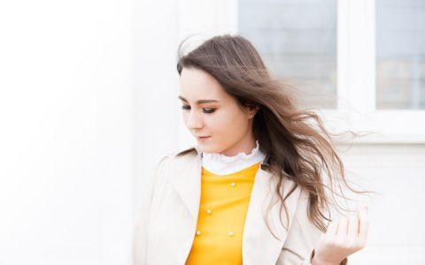 Wiosenna damska, kobieca stylizacja z beżowym płaszczem, żółtą bluzką, ciemnymi jeansami i butami Reebok Classic Club